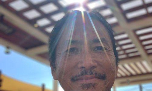 Photograph of Govinda Kai with sunshine streaming behind him.